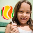 Portrait of pretty female child with lollipop smiling — Stock Photo #11891429