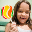 Portrait of pretty female child with lollipop smiling - Stock Photo