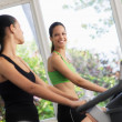 Pretty young girls training on fitness bikes in gym — Stock Photo