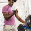 Young black man taking weights from rack in gym - Stock Photo