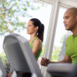 Stock Photo: Young exercising and running on treadmill in gym