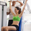 Personal trainer helping woman training in wellness club — Stock Photo
