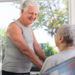 Active senior friends talking and working out in fitness club - Stock Photo