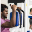 Stock Photo: Young african american man training in fitness gym