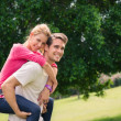 Young couple running piggyback in city park — Stock Photo