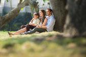 Lycklig familj i stadens trädgårdar avkopplande under helgdagar — Stockfoto