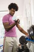 Genç siyah erkek spor salonunda ağırlık raf alarak — Stok fotoğraf