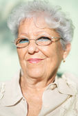 Old woman with eyeglasses smiling and looking at camera — Stock Photo