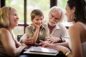 Happy parents and grandparents with boy in bar — Stock Photo
