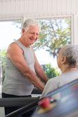 Aktywne starszy przyjaciele mówić i pracy w klubie fitness — Zdjęcie stockowe