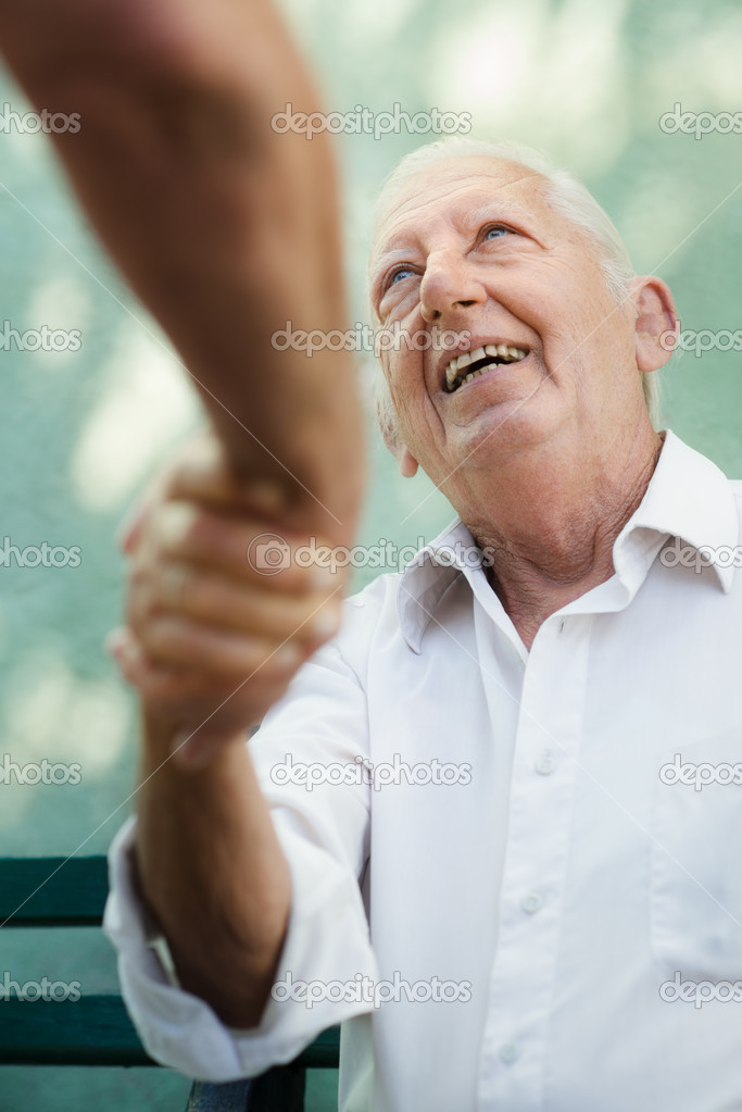 Active retirement, two old male friends talking and shaking hands on bench in public park — Stock Photo #11891911