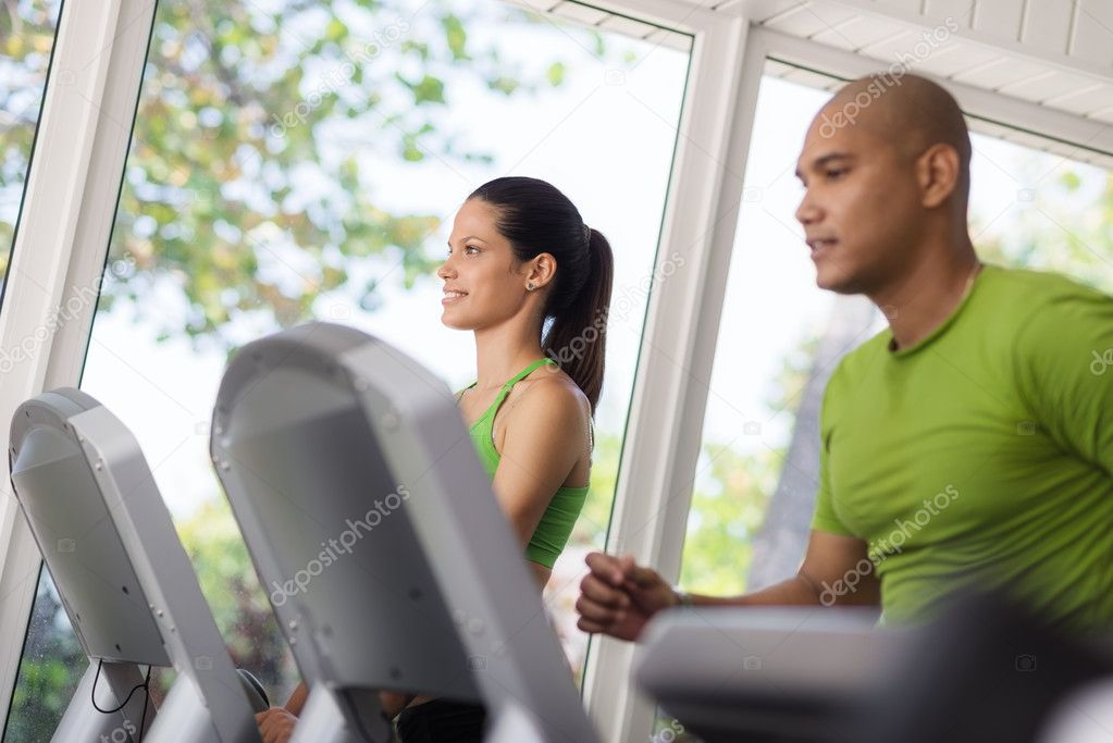 Man and woman working out and running on treadmill in fitness club — Stock Photo #11892588