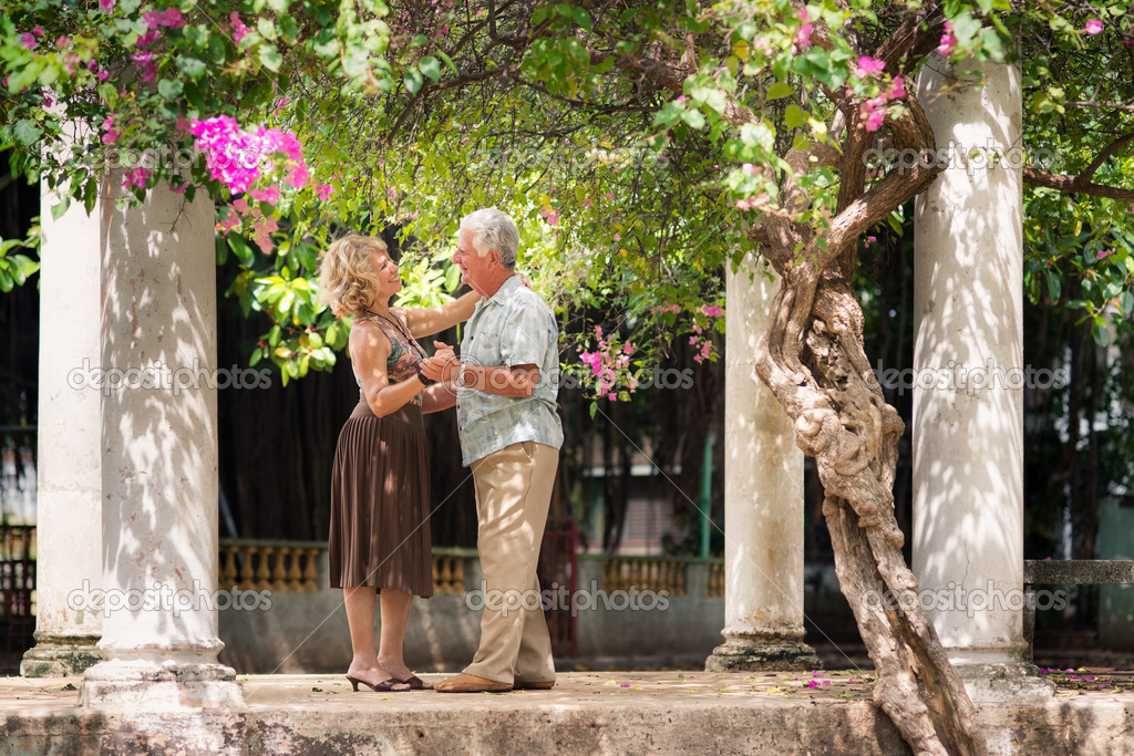 Active retired having fun, happy old man and woman dancing latin american dance in patio — Stock Photo #11893206