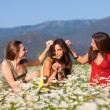 Three girls on camomile field — Stock Photo