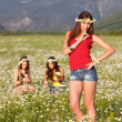 Three girls on camomile field - Stock Photo