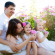 Family in rose flowers — Stock Photo #11011436