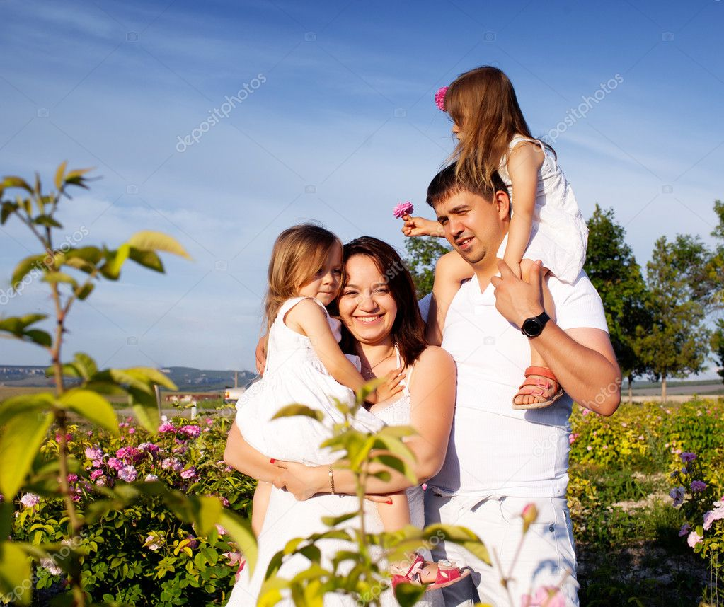 Family in rose flowers garden  Stock Photo #11092537