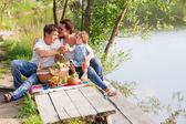 Family on the picnic near the lake — Stock Photo