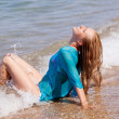 Girl sitting on the seashore - Stockfoto