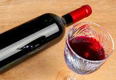 Bottle of wine and a glass on a wooden table — Stock Photo