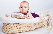 Little sweet girl a baby lying on a beautiful cushion in a wicke — Stock Photo