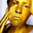 Royalty-Free Stock Photo: The boy&#039;s head painted with gold paint stares into the camera.
