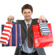 Man in suit stretching hand with shopping bags — Stock Photo