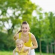 Portrait of happy mother and baby girl in park — Stok Fotoğraf #11557201