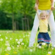 Mother playing with baby girl on dandelions field — Stock Photo