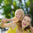 Stock Photo: Happy baby girl piggybacking mother
