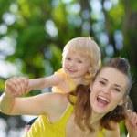 Happy baby girl piggybacking mother — Stock Photo