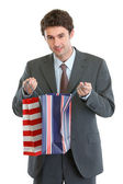 Man in suit looking into shopping bag — Stock Photo