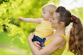 Outdoors portrait of mother and baby girl pointing in corner — Stock Photo