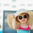 Portrait of baby in hat and glasses sitting on sun bed — Stock Photo #11564762
