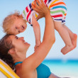 Stock Photo: Happy mother playing with baby on sunbed