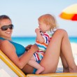Portrait of happy mother and baby on sun bed — Stock Photo