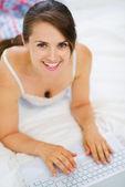 Usmívající se žena položila na postel a pracují na notebooku. horní pohled — Stock fotografie