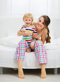 Portrait of smiling mother and baby in bedroom — Stock Photo
