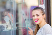 Smiling woman pointing on showcase — Stock Photo