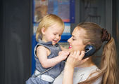 Mother and baby talking phone in city — Stock Photo