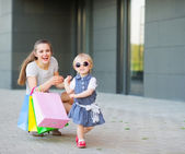 Fashion-monger baby on shopping with mom wear new glasses — Stock Photo
