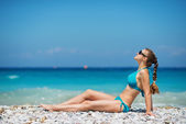 Woman in sunglasses enjoying sunshine on beach — Stock Photo