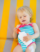 Baby laying on sun bed with sun block bottle — Stock Photo