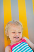Portrait of laughing baby laying on sunbed — Stock Photo