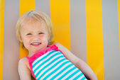 Portrait of happy baby laying on sun bed — Stock Photo