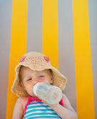 Baby laying on sun bed and drinking from bottle — Stock Photo