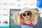 Portrait of baby in hat and glasses sitting on sun bed — Stock Photo