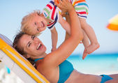 Portrait of mother playing with baby on beach — Foto Stock