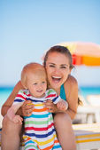 Portrait of happy mother and baby on beach — Stock Photo