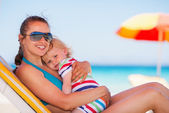 Happy mother laying on sun bed and hugging baby — Stock Photo